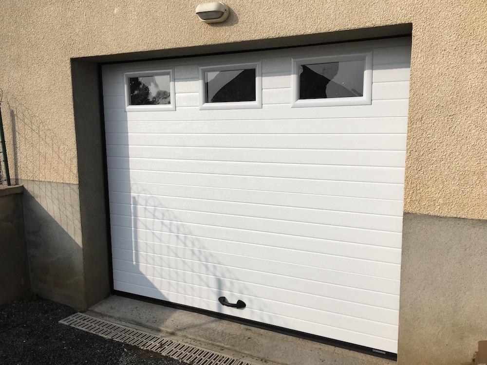 Porte de garage rainurée blanche avec hublots